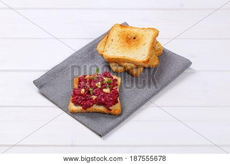 toasts with fresh beetroot spread on grey place mat