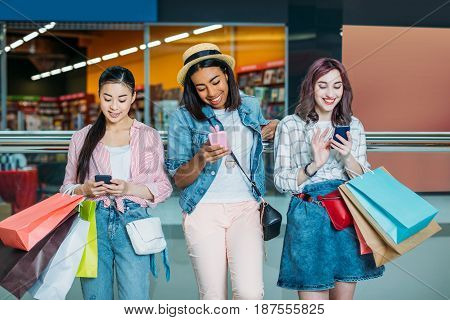 Smiling Young Women With Shopping Bags Using Smartphones, Young Girls Shopping Concept