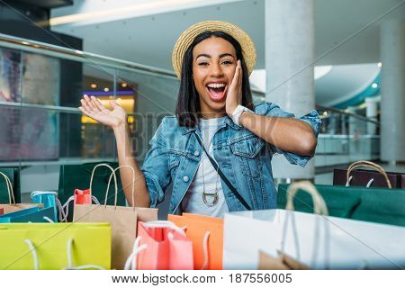 Shocked Young Woman Looking At Colorful Shopping Bags, Boutique Shopping Concept
