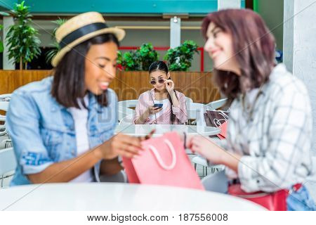 Young woman looking at smiling friends with shopping bag young girls shopping concept