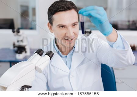 Delightful brunette. Attractive medical worker raising his left hand and holding test-tube while keeping smile on his face