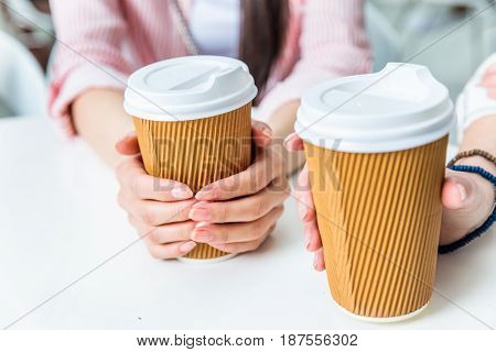 Partial View Of Women Holding Cups Of Coffee In Hands