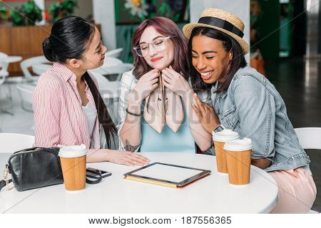 Smiling Young Women Sitting At Table With Paper Cups And Holding New Stylish Shoes, Young Girls Shop