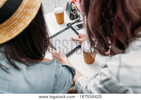 friends using digital tablet while sitting in cafe after shopping