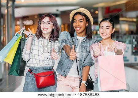 Portrait Of Smiling Women With Shopping Bags Showing Thumbs Up Signs At Shopping Mall