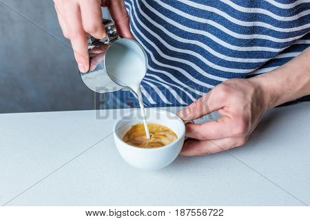 Partial Close Up View Of Man Pouring Milk Into Coffee