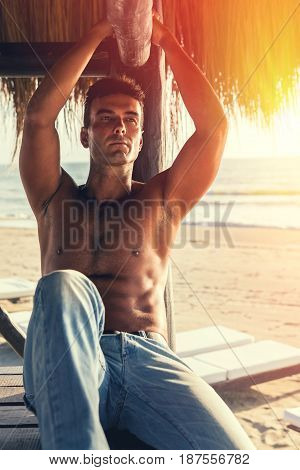 Handsome sexy male outdoor on the beach. A handsome male shirtless in jeans relaxed seaside. Sunset and warm lighting. Concept of male beauty, vacation and relaxation.