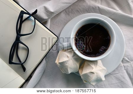 Coffee with dessert and a notepad with glasses