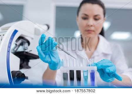 Cautious person. Serious young researcher holding medical instrument in right hand looking downwards while touching support
