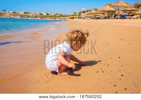 Baby playing with sand on the surf edge by the sea on the beach.