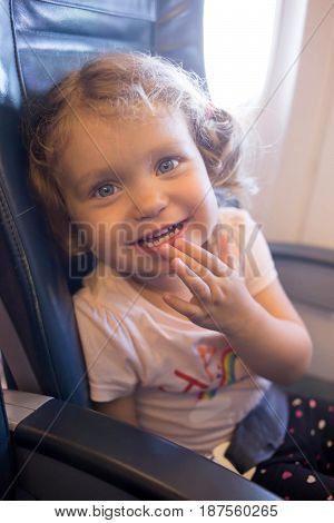 Little laughing girl is traveling by plane. A small smiling child is a passenger of an airplane.