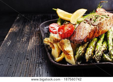 Recipe - delicious portion of grilled salmon fillet with asparagus tomatoes artichoke spices on a black wooden board. Close up copyspace selective focus.
