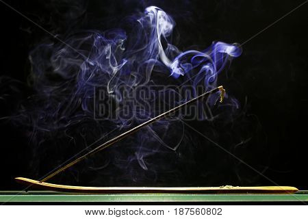 Incense stick smolders and emits intensive smoke various forms