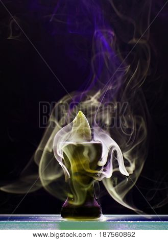 Aromatic cone smoldering in a ceramic stand and emits smoke of different colors and intensity