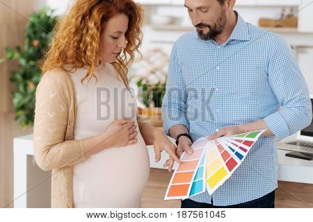 Hard decision. Full term pregnant woman choosing a wallpaper colour from a palette while discussing future home renovation with a husband.