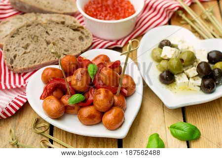 Mini Frankfurter sausage hot-dog in sour sweet sauce with bell pepper for tapas