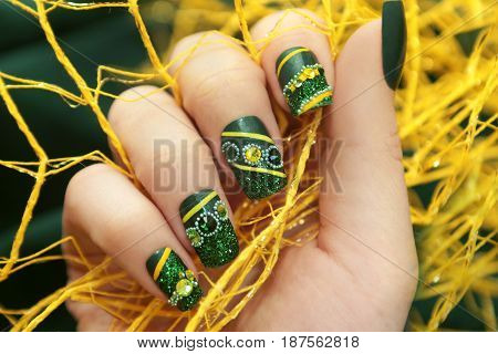 Green manicure square shape nail glitter,rhinestones and yellow lines a close-up.
