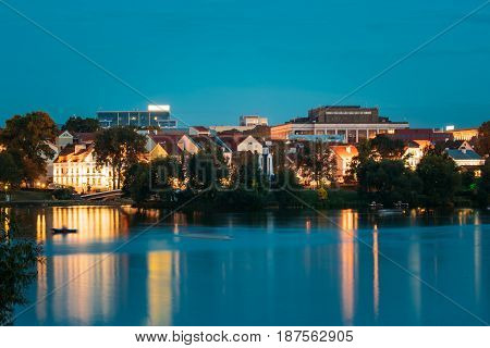 Minsk, Belarus. Landmarks At Summer Evening In Night Lights Illumination. Trinity Suburb Trojeckaje Pradmiescie And Island Of Tears Island Of Courage And Sorrow, Ostrov Slyoz