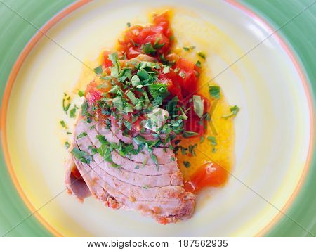 Fillet of tuna cooked in pan with tomato oil and parsley. Ready to eat