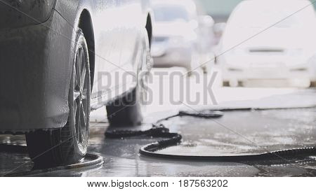 Washing the car in workshop - automobile in foam, telephoto