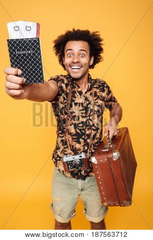 Image of young cheerful african man standing isolated over yellow background. Looking at camera holding passport and suitcase. Focus on passport.