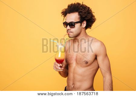 Picture of young african man dressed in shorts standing isolated over yellow background. Looking aside drinking cocktail.