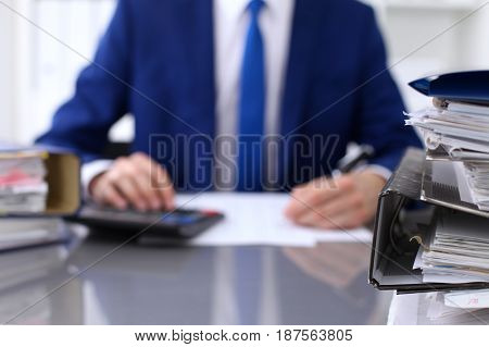 Binders with papers are waiting to be processed with businessman back in blur. Accounting planning budget, audit, insurance and business concept.