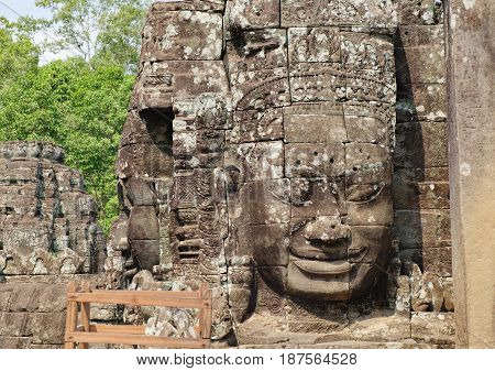The wooden scaffolding for the reconstruction of smiling stone faces of Prasat Bayon the central temple of Angkor Thom Complex, Siem Reap, Cambodia. Ancient Khmer architecture for restoration.