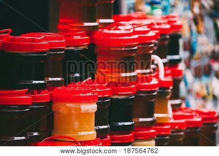 Various Jars With Sweet Tasty Yummy Jams Stading In Rows. Jam Made From Walnuts, Pine Cones, Walnuts, Honey. Traditional Healthy Cuisine