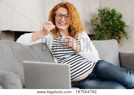 Healthy nutrition. Redhead mature future mom relaxing on a sofa, surfing the Internet and enjoying Greek yogurt for dessert.