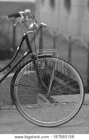 Black bicycle with white wheels on a blurred city background.