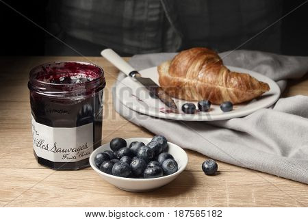 Morning blueberry with croissant and blueberry jam on a wooden table. Jam Wild Blueberries