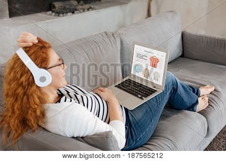 Fashionable pregnancy. Mother-to-be relaxing at home, listening to her favourite music and buying clothes online.
