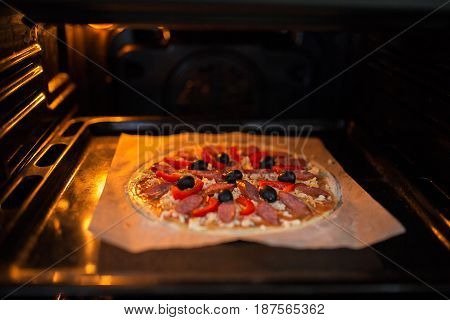 Fresh pizza on a metal baking tray in hot oven