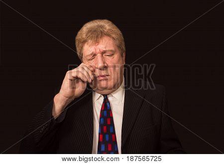 Stressed senior caucasian businessman rubbing eyes against black studio background