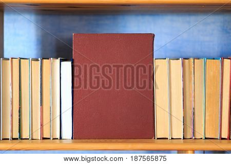 Books On The Wooden Shelf Turned By A Cover Back