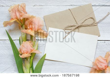 blank white greeting card with tender iris flowers bouquet and envelope with flower buds on white wooden background. top view. mock up
