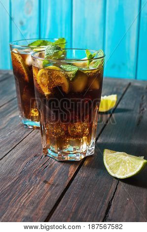 Homemade Cuba Libre with fresh lime brown rum and crushed ice on an old wooden table.