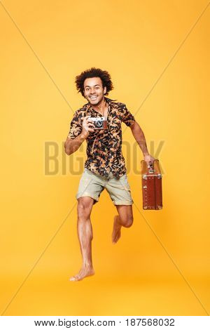 Full length portrait of a cheerful young african man in summer clothes jumping and taking photo with retro camera isolated over yellow background