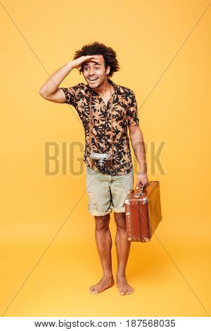 Full length portrait of a smiling afro american man with suitcase keeping hand on his forehead and looking forward isolated over yellow background