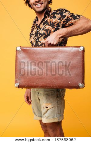 Cropped image of a smiling african guy showing suitcase isolated over yellow background