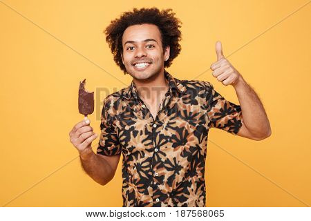 Portrait of a happy afro american man holding ice cream and showing thumbs up gesture isolated over yellow background
