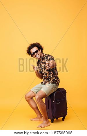 Full length portrait of a cheerful young african tourist guy in sunglasses sitting on a suitcase and pointing finger at camera isolated over yellow background