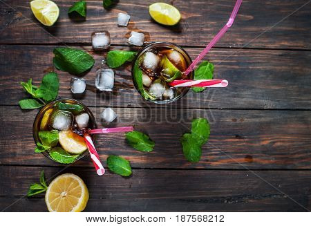 Homemade Cuba Libre with fresh lime brown rum and crushed ice on an old wooden table. Top view and copyspace poster