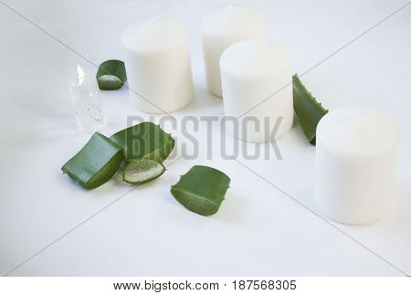 Organic cosmetics photo. White wax candles and aloe vera. Eco products for skin care. Selective focus.