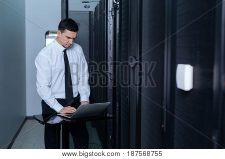 Innovative device. Handsome nice good looking man standing in front of the laptop and working on it while being in the server room