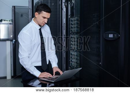 Modern laptop. Nice pleasant adult man standing in front of the laptop and typing while checking the information