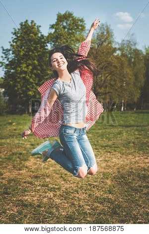Young fitness girl in modern casual clothes jumping outdoors. Dressed in a gray shirt, blue jeans and a Tshirt in a red cage