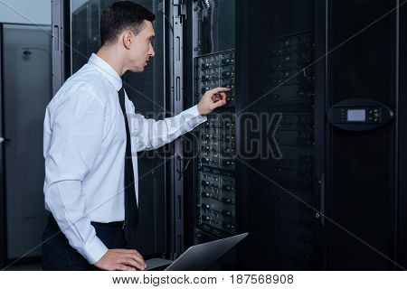 At work. Pleasant nice handsome man standing in front of the network server and pressing the button while working in the data center