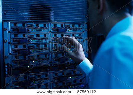 True professional. Nice professional experienced engineer looking at the network server and checking it while working in the data center